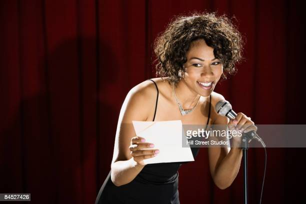 Mixed race woman announcing winner on stage