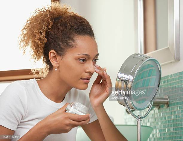 mixed race woman applying eye cream - vanity mirror stock pictures, royalty-free photos & images