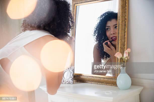Mixed race woman applying lipstick in mirror