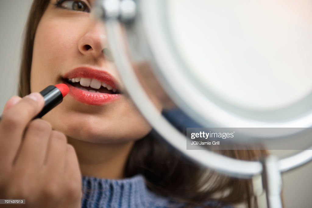 Mixed Race woman applying lipstick in mirror : Stock Photo