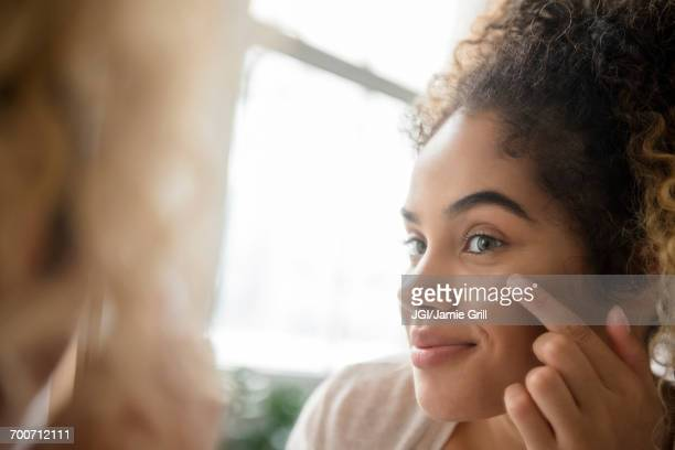 Mixed Race woman applying lotion to cheek