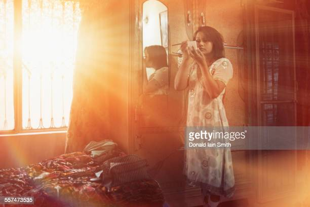mixed race woman applying makeup in bedroom - punjab pakistan stock photos and pictures