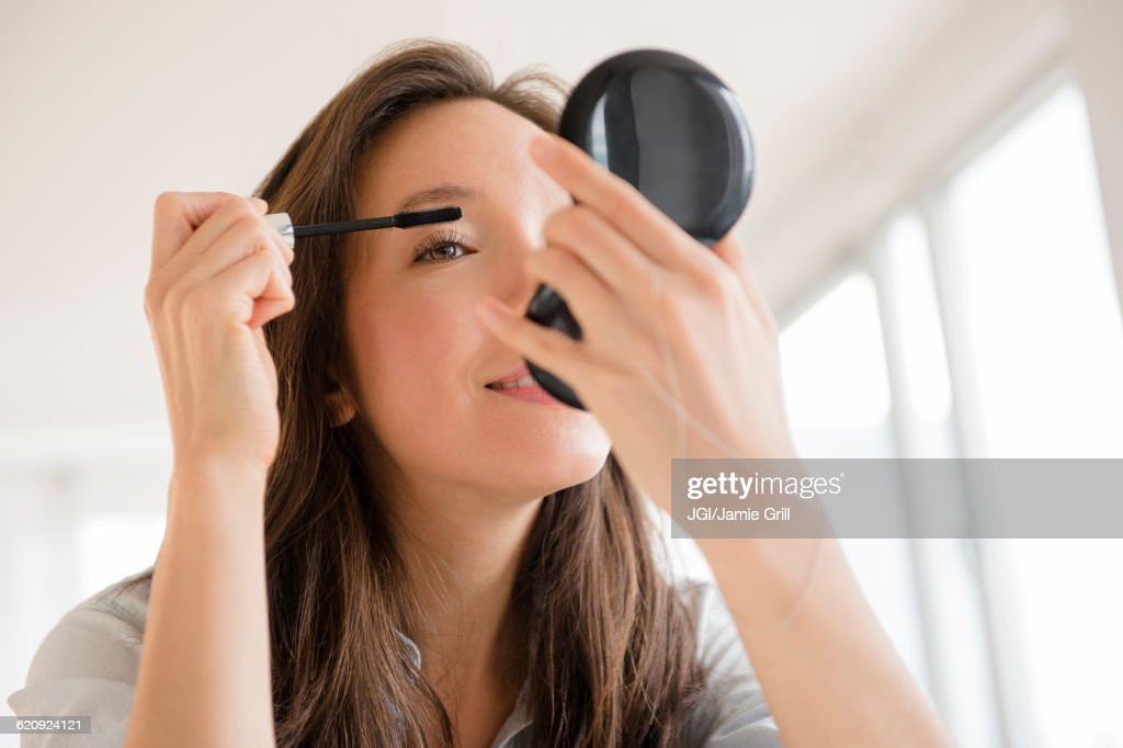 Mixed race woman applying makeup in compact mirror : Stock Photo