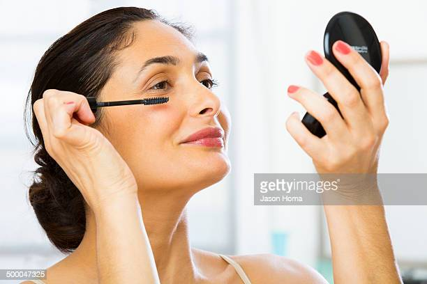 Mixed race woman applying makeup