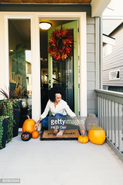 mixed race woman arranging pumpkins on patio - autumn decoration stock pictures, royalty-free photos & images