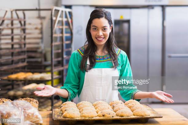 Mixed race woman baking in industrial kitchen