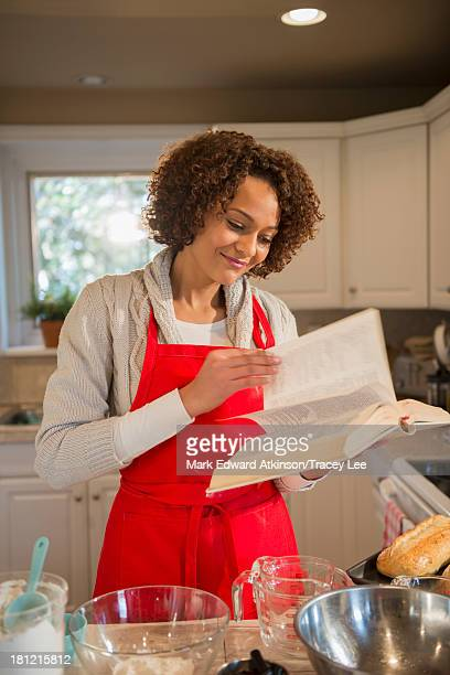 Mixed race woman baking in kitchen