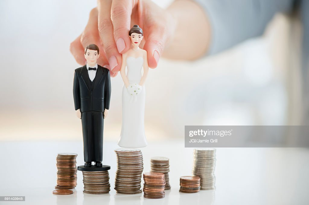 Mixed race woman balancing bride and groom statues on coin stacks : Stock Photo