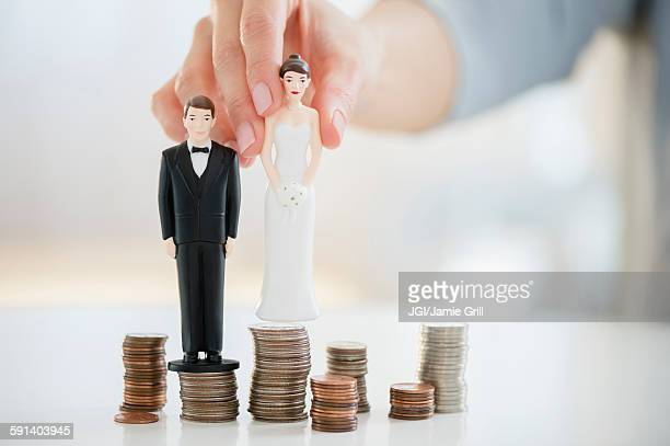 mixed race woman balancing bride and groom statues on coin stacks - penny for the guy stock photos and pictures