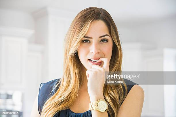 Mixed race woman biting her nail