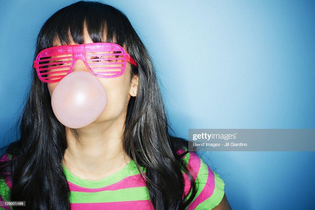 Mixed race woman blowing bubble with bubble gum : Foto de stock