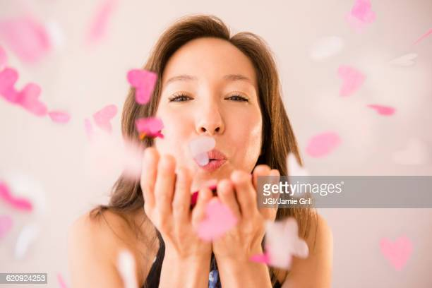 Mixed race woman blowing confetti