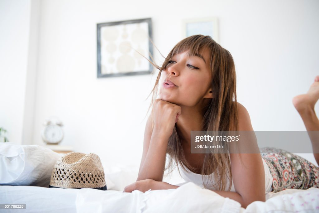 Mixed race woman blowing hair from face : Stock Photo