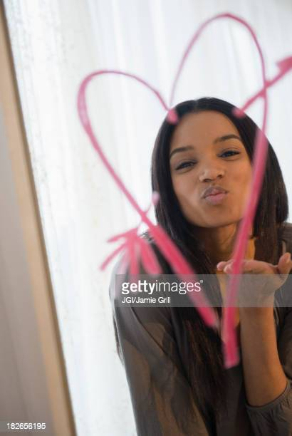 Mixed race woman blowing kiss in mirror