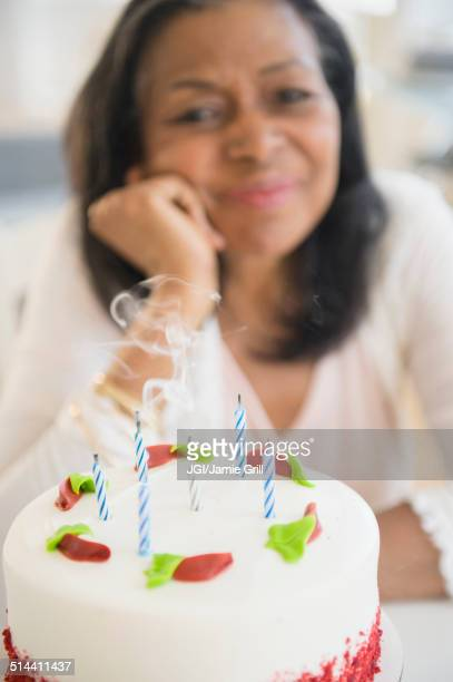 Mixed race woman blowing out birthday candles on cake