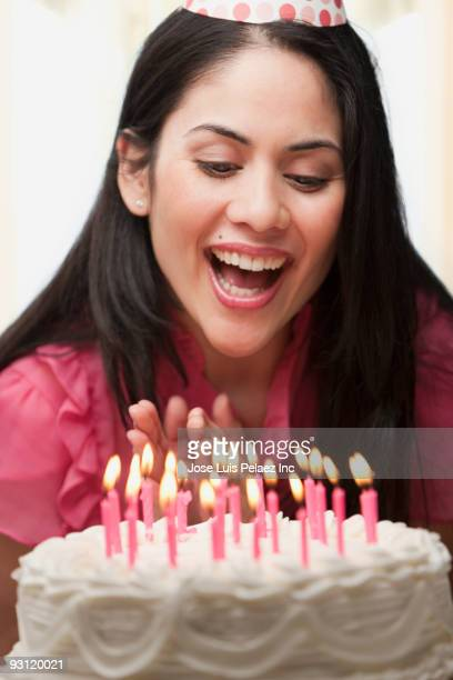 Mixed race woman blowing out candles on birthday cake
