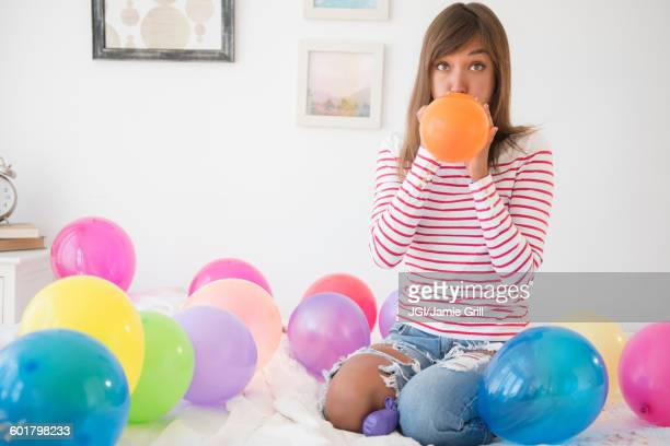 Mixed race woman blowing up balloons