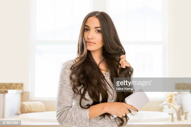 mixed race woman brushing hair in bathroom - long hair stock pictures, royalty-free photos & images