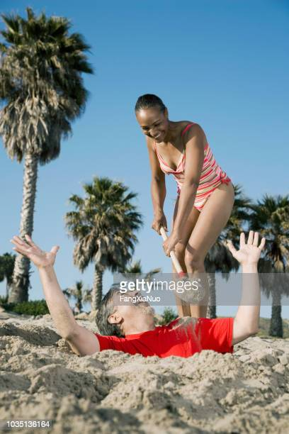 mixed race woman burying husband in sand - enterrar imagens e fotografias de stock