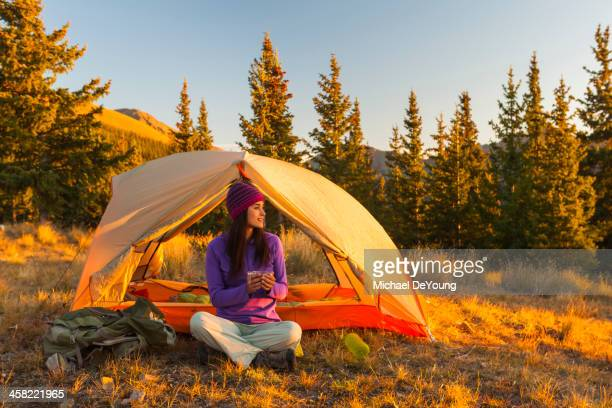 Mixed race woman camping in rural landscape