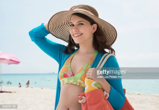 mixed race woman carrying bag on beach - woman carrying tote bag stock photos and pictures