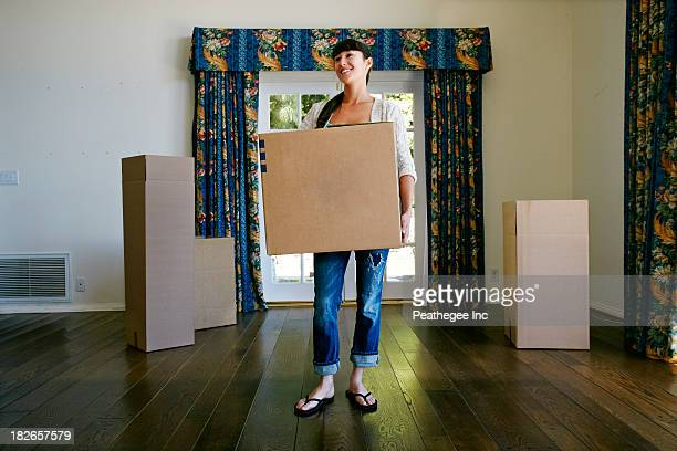 Mixed race woman carrying box in new home
