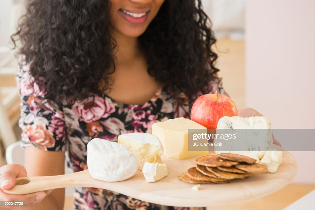 Mixed race woman carrying fruit and cheese board : Stock Photo