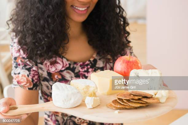 Mixed race woman carrying fruit and cheese board