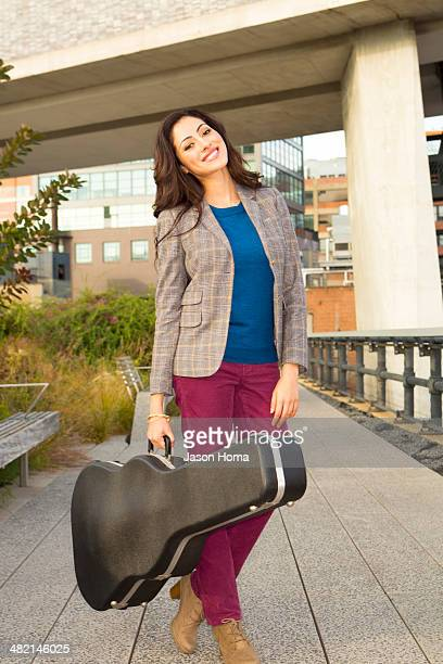 Mixed race woman carrying guitar case