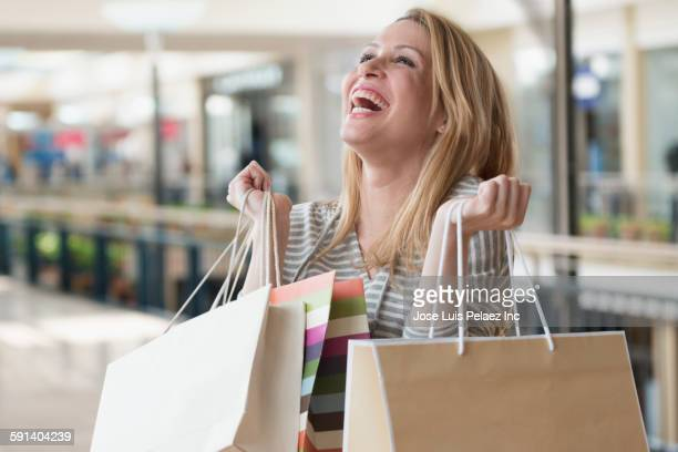 Mixed race woman carrying shopping bags in mall