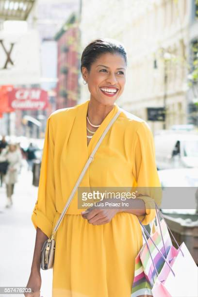 Mixed race woman carrying shopping bags on city sidewalk
