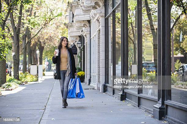 mixed race woman carrying shopping bags - pavement stock pictures, royalty-free photos & images