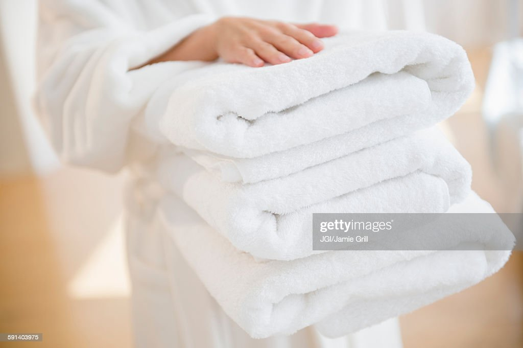 Mixed race woman carrying stack of clean towels : ストックフォト