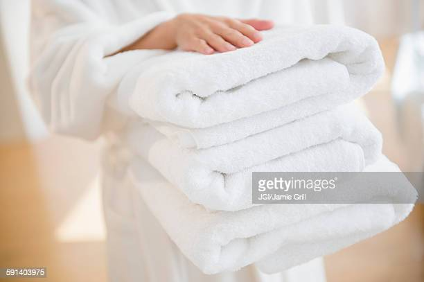 mixed race woman carrying stack of clean towels - morbidezza foto e immagini stock