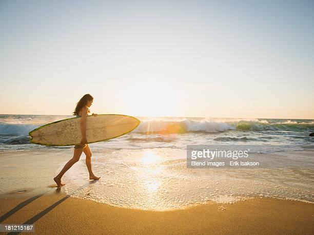 mixed race woman carrying surfboard on beach - california stock pictures, royalty-free photos & images