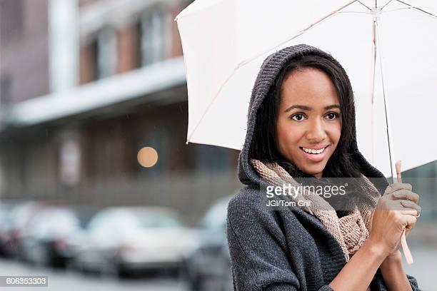 Mixed race woman carrying umbrella outdoors