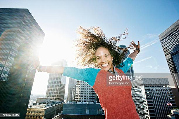 Mixed race woman cheering with arms outstretched on urban rooftop