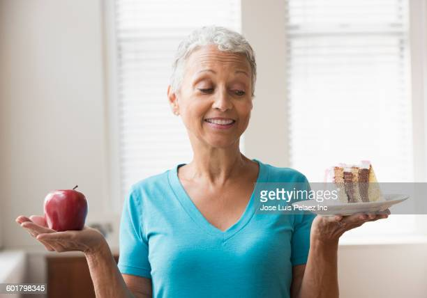 Mixed race woman choosing apple or cake