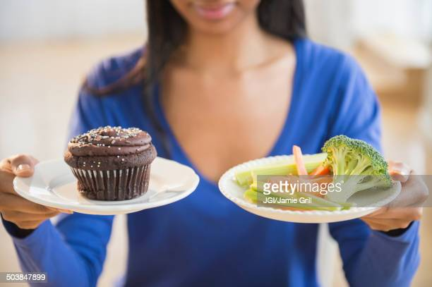mixed race woman choosing vegetables or cupcake - unhealthy eating stock pictures, royalty-free photos & images