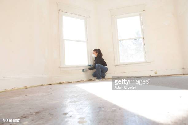 Mixed race woman cleaning wall in new home
