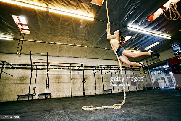Mixed Race woman climbing rope in gymnasium