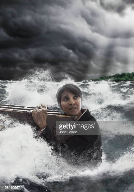 Mixed race woman clinging to trunk in stormy sea