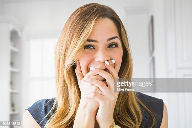 Mixed race woman covering her mouth at home