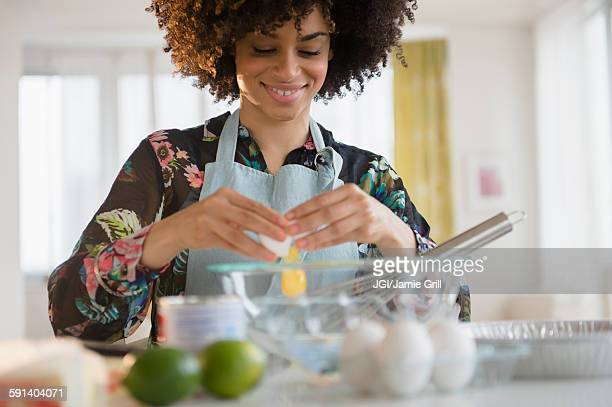 Mixed race woman cracking egg