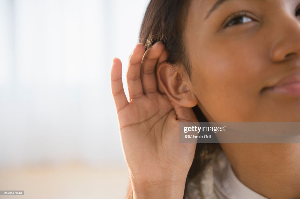 Mixed race woman cupping her ear : Stock Photo