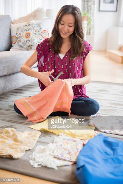 Mixed race woman cutting up clothing