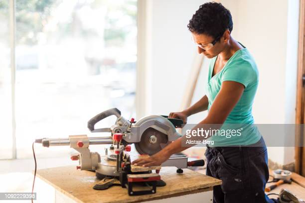 mixed race woman cutting wood with an electric power saw - mitre stock pictures, royalty-free photos & images