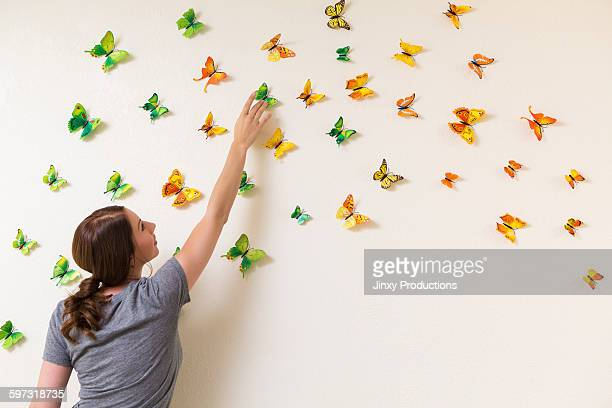 Mixed race woman decorating wall with butterflies