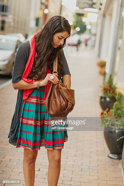 Mixed race woman digging in purse on city street