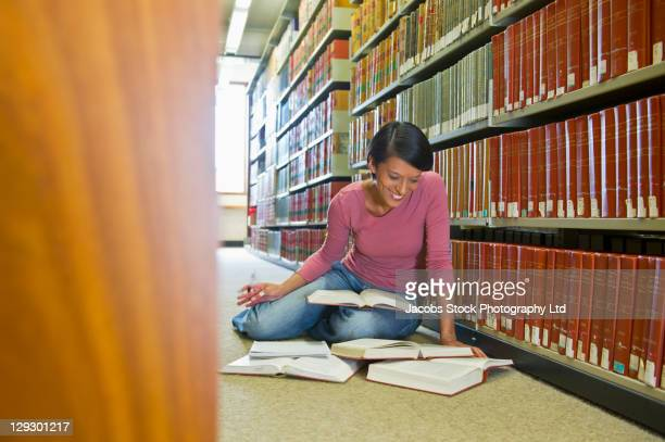 Mixed race woman doing research in library